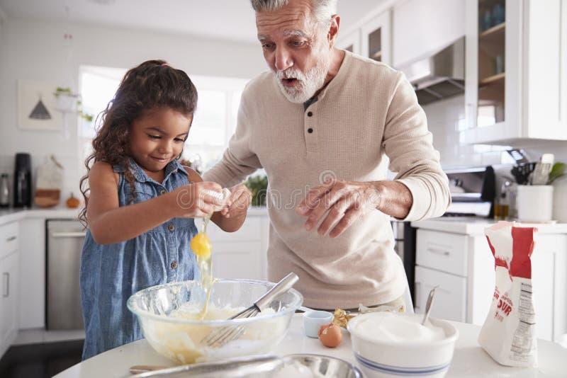 Junges Mädchen, das ein Ei in Kuchenmischung mit ihrem Großvater am Küchentisch, Abschluss oben bricht lizenzfreie stockbilder