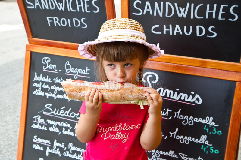 Junges Mädchen, das ein großes Sandwich isst lizenzfreie stockbilder