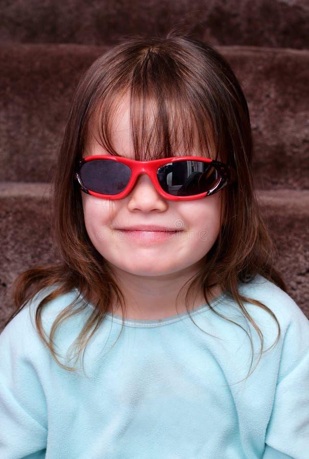 Junges Mädchen, das ein mit Sonnenbrillen zuhause kühl schaut stockfoto