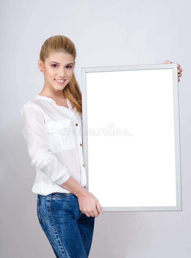 Junges Mädchen, das ein weißes leeres Brett lächelt und hält. stockfotos