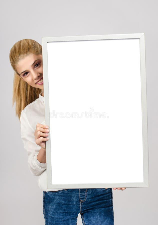 Junges Mädchen, das ein weißes leeres Brett lächelt und hält. stockfoto