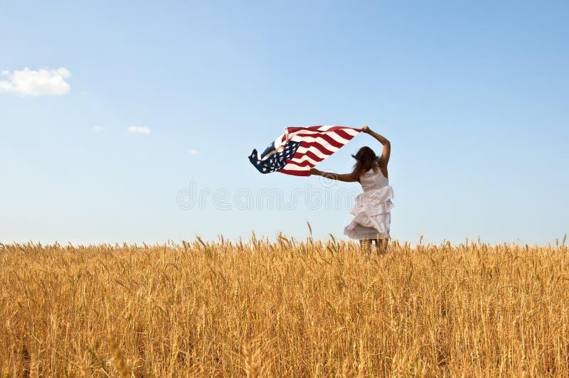 Junges Mädchen, das eine amerikanische Flagge anhält stockfotos