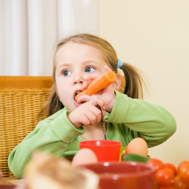 Junges Mädchen, das eine Karotte isst lizenzfreies stockfoto