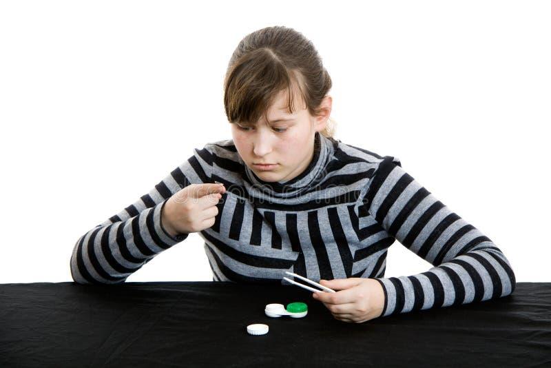 Junges Mädchen, das eine weiche Kontaktlinse im Auge einsteckt stockbilder