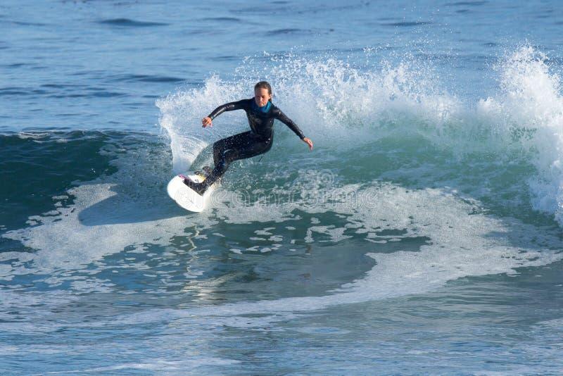 Junges Mädchen, das eine Welle in Kalifornien surft lizenzfreie stockfotos