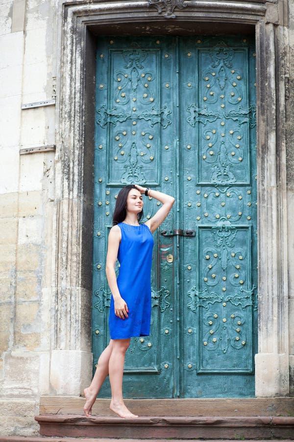 Junges Mädchen, das in einem blauen Kleid für die Kamera auf einem Hintergrund der grünen Metalltür aufwirft Überzeugte stilvolle stockfotografie