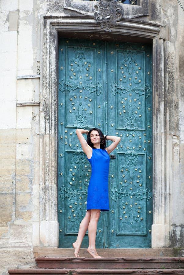 Junges Mädchen, das in einem blauen Kleid für die Kamera auf einem Hintergrund der grünen Metalltür aufwirft Überzeugte stilvolle stockbild