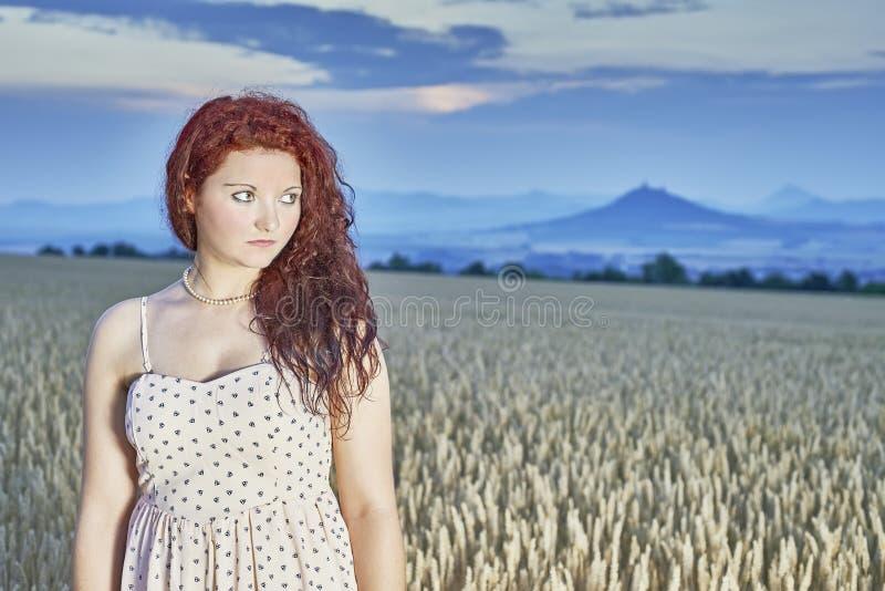 Junges Mädchen, das in einem Getreidefeld steht stockfotografie