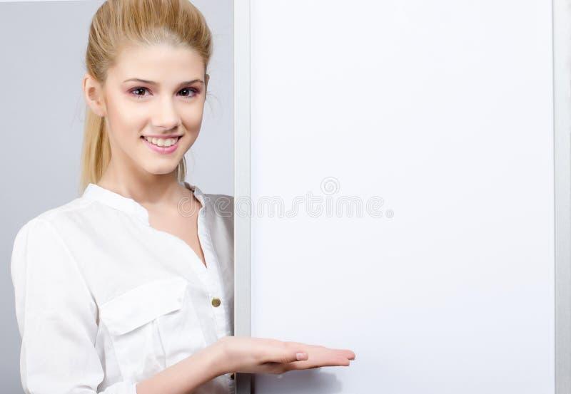 Junges Mädchen, das einem weißen leeren Brett lächelt und darstellt. stockbild