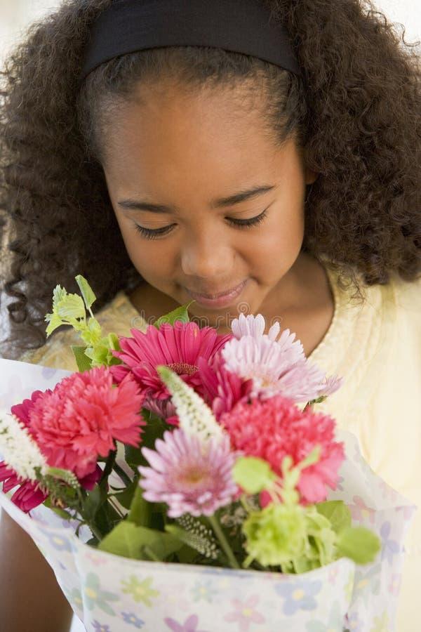 Junges Mädchen, das einen Blumenstrauß der Blumen riecht lizenzfreie stockbilder