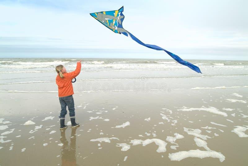 Junges Mädchen, das einen Drachen an der Küstenlinie fliegt lizenzfreie stockfotos