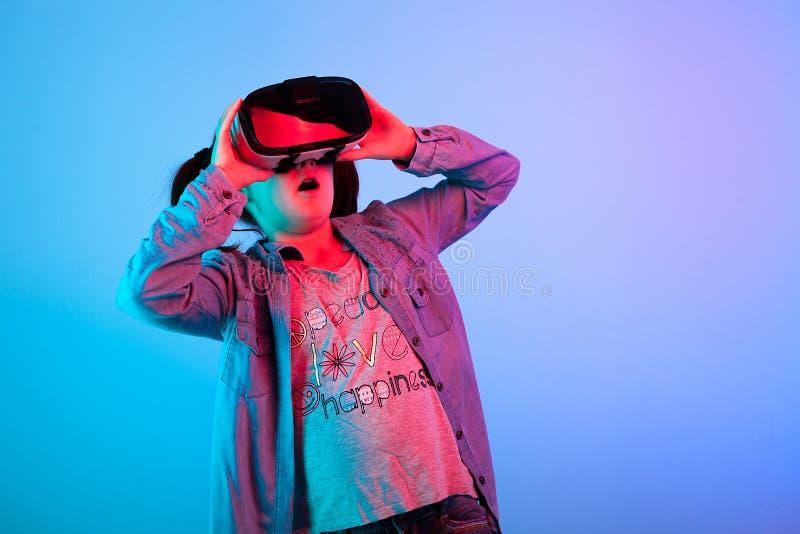 Junges Mädchen, das einen Film auf VR-Kopfhörer aufpasst stockfotografie