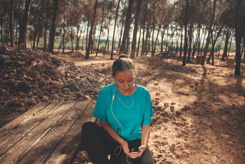 Junges Mädchen, das in einer hörenden Musik der Bank in ihrem Mobiltelefon sitzt stockfotos
