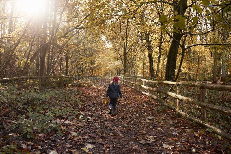 Junges Mädchen, das entlang Weg durch Autumn Countryside geht lizenzfreie stockfotos
