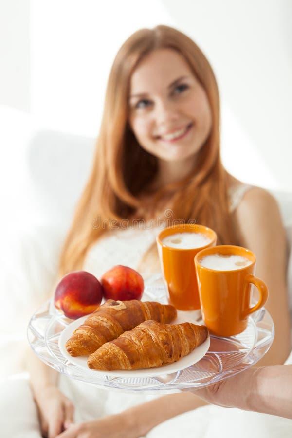 Junges Mädchen, das Frühstück im Bett isst stockfoto