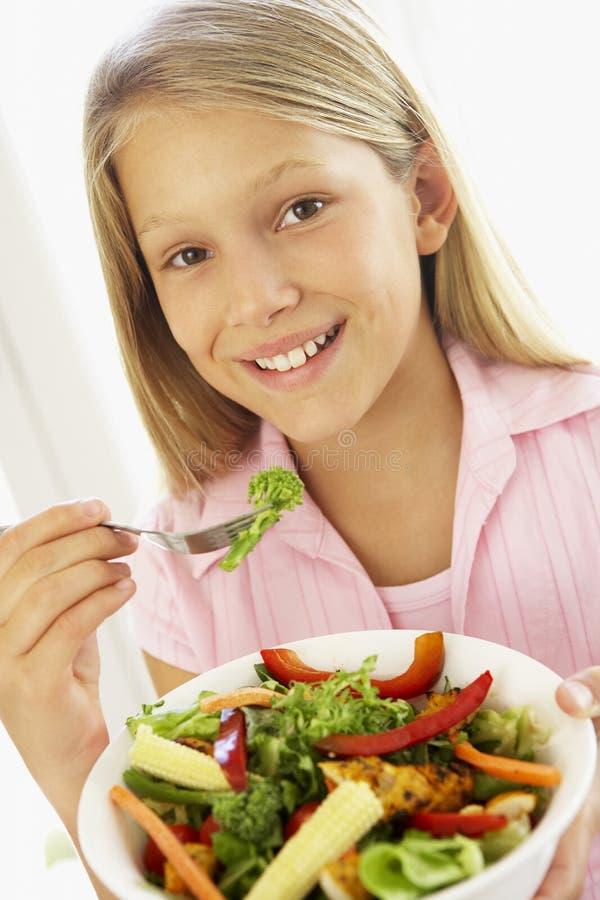 Junges Mädchen, das frischen Salat isst lizenzfreies stockfoto