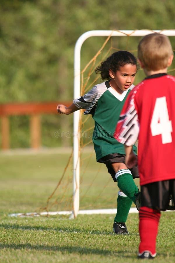 Junges Mädchen, das Fußball spielt stockbild