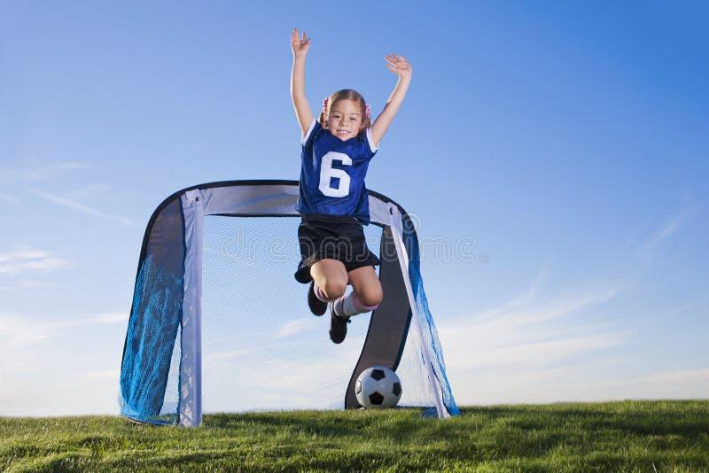 Junges Mädchen, das Fußball spielt und Ziel zählt lizenzfreies stockfoto
