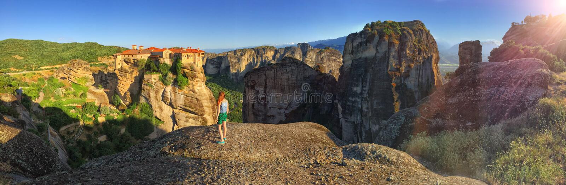 Junges Mädchen, das Gebirgs-und Kloster-Panoramablick Meteora bewundert stockbild