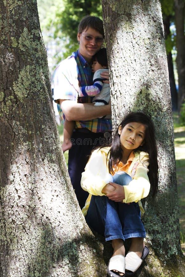 Junges Mädchen, das gegen Baum sitzt lizenzfreies stockbild