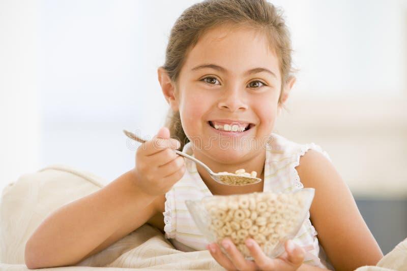 Junges Mädchen, das Getreide beim Wohnzimmerlächeln isst lizenzfreies stockbild