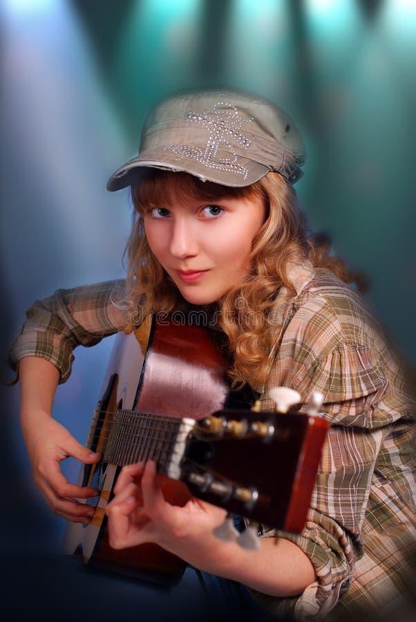 Junges Mädchen, das Gitarre auf dem Stadium spielt lizenzfreies stockbild