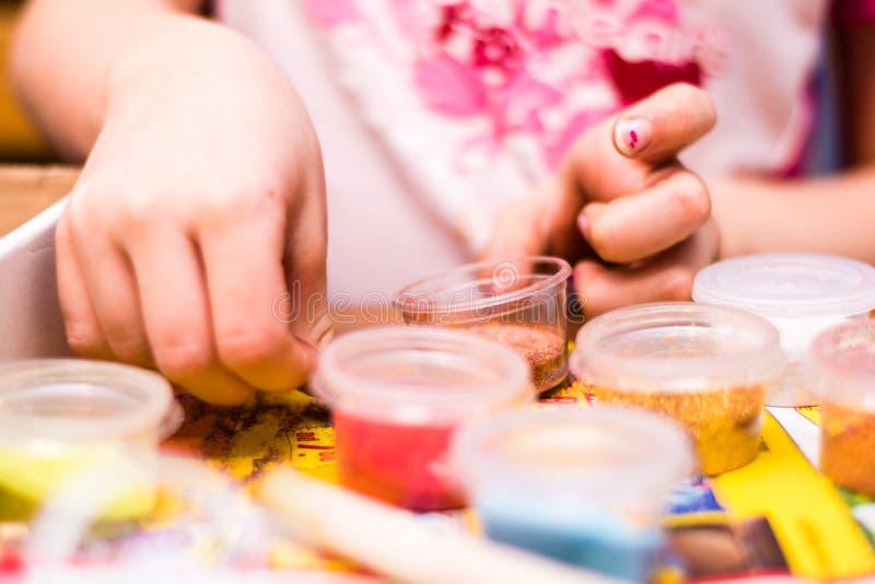 Junges Mädchen, das handgemachte Kunst spielt und macht stockfoto