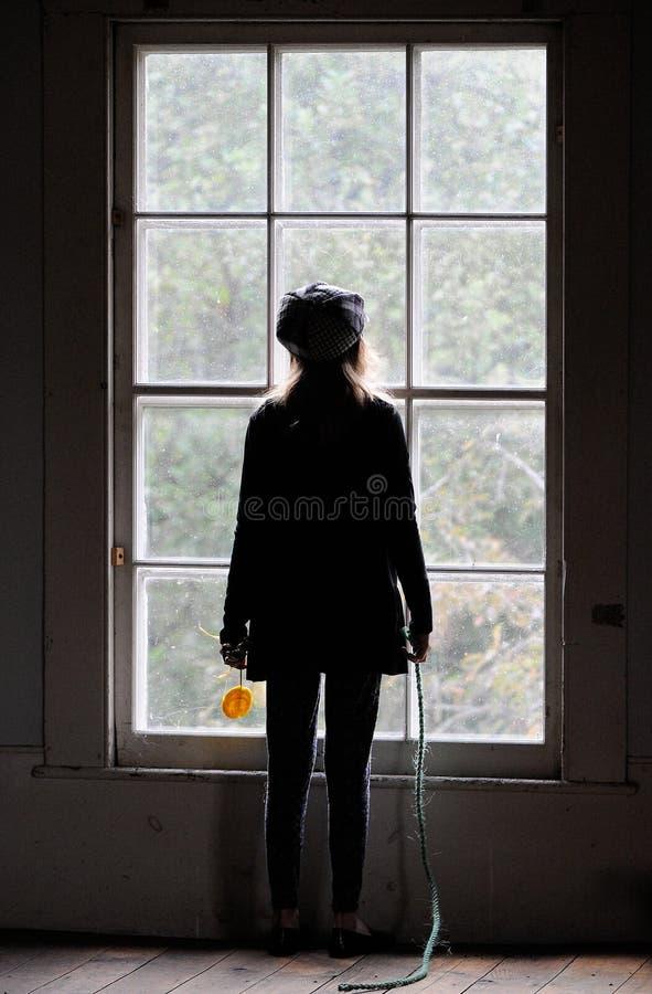 Junges Mädchen, das heraus Fenster schaut. stockbild