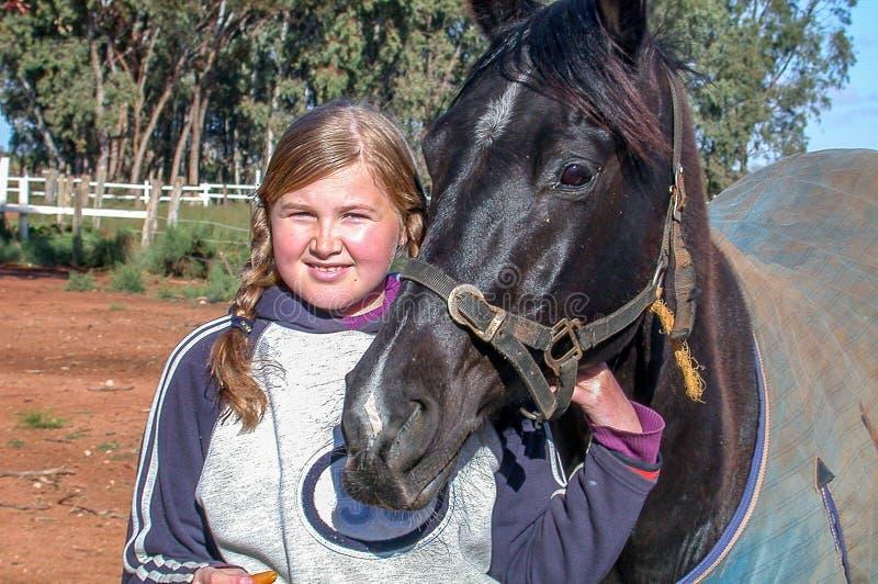 Junges Mädchen, das ihr Pferd hält stockbilder