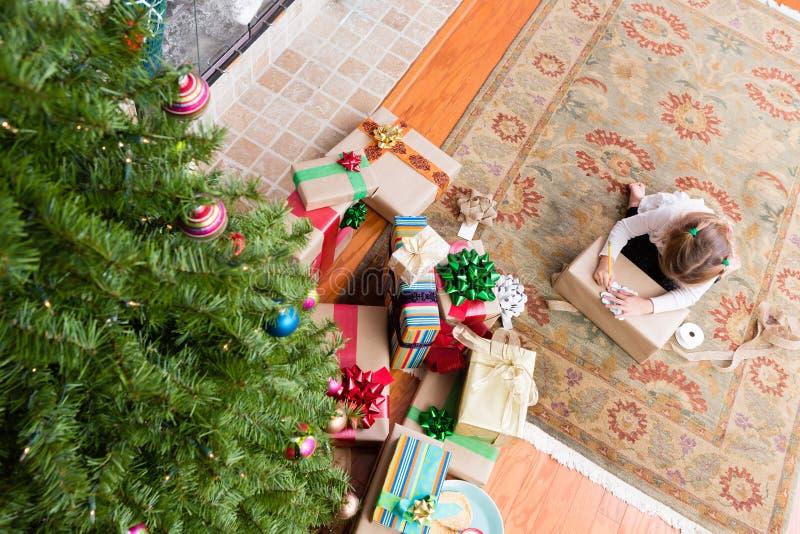 Junges Mädchen, das ihre Familie Weihnachtsgeschenke einwickelt stockfotos
