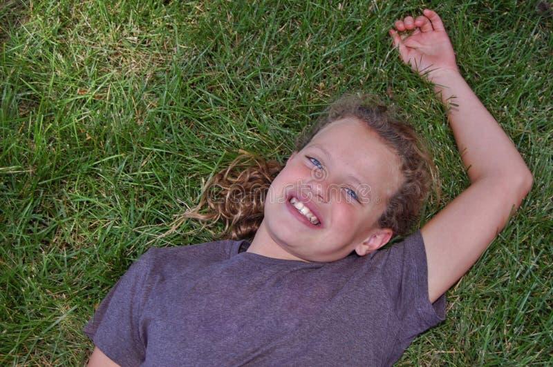 Junges Mädchen, das im Gras sich entspannt lizenzfreies stockbild