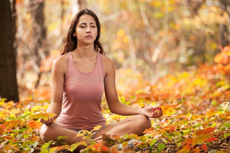 Junges Mädchen, das im Herbstpark meditiert stockfotografie