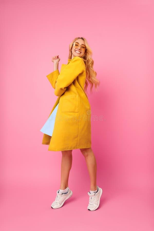 Junges Mädchen, das im Mantel, Spaß auf rosa Hintergrund habend aufwirft stockfotografie