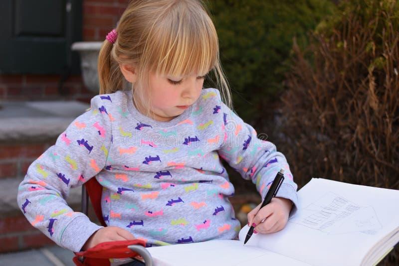 Junges Mädchen, das im Notizbuch skizziert lizenzfreie stockbilder