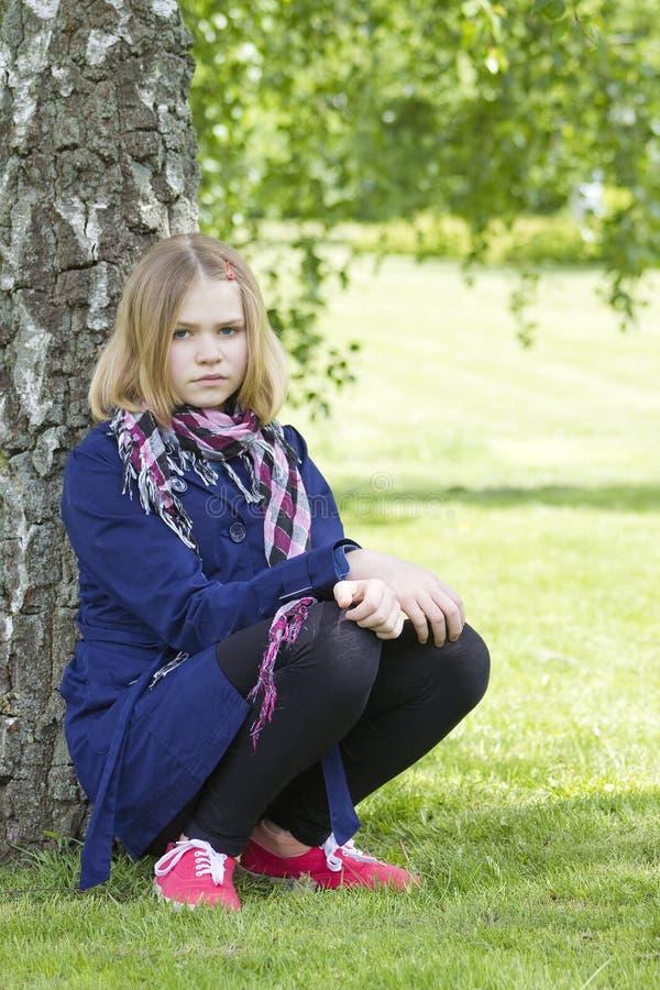 Junges Mädchen, das im Park stillsteht stockfotografie