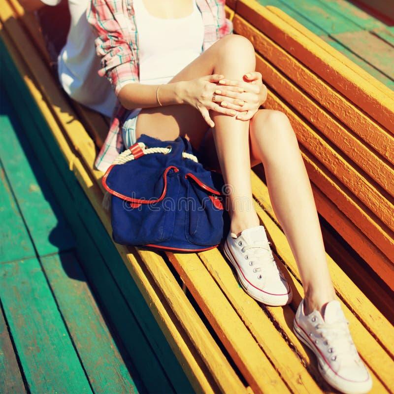 Junges Mädchen, das im Stadtpark auf Bank, schöne schlanke weibliche Beine am Sommer stillsteht lizenzfreie stockbilder