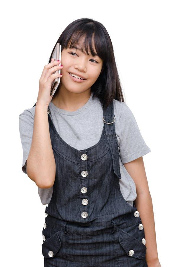 Junges Mädchen, das am intelligenten Telefon über Weiß spricht stockbild