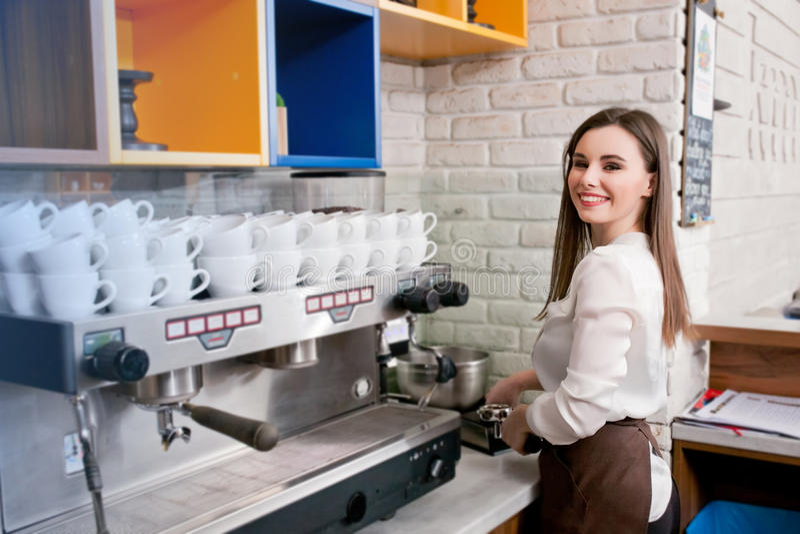 Junges Mädchen, das Kaffee in einem Café barista zubereitet stockfotografie