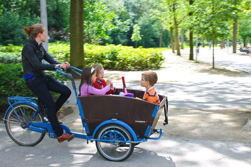 Junges Mädchen, das Kinder im Wagen transportiert. stockfoto