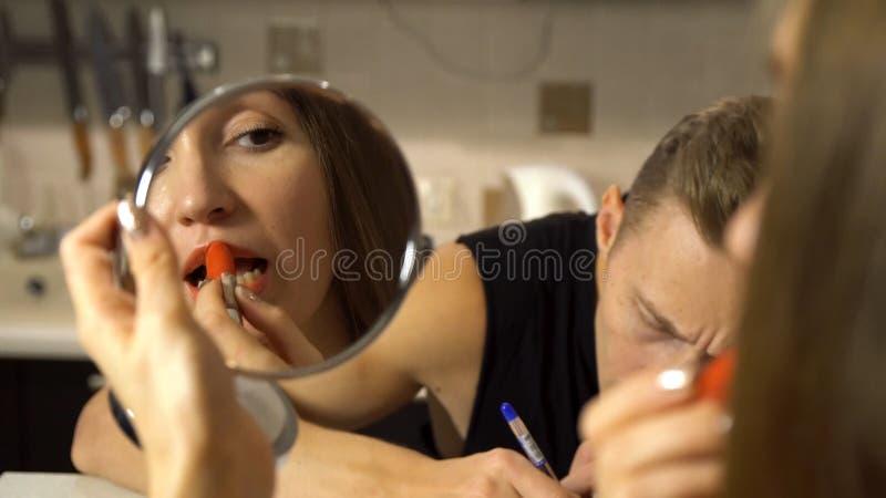 Junges Mädchen, das kosmetischen Lippenstift, einen kleinen Spiegel betrachtend nahe ihrem Freund anwendet, der an einem Tisch un lizenzfreies stockfoto