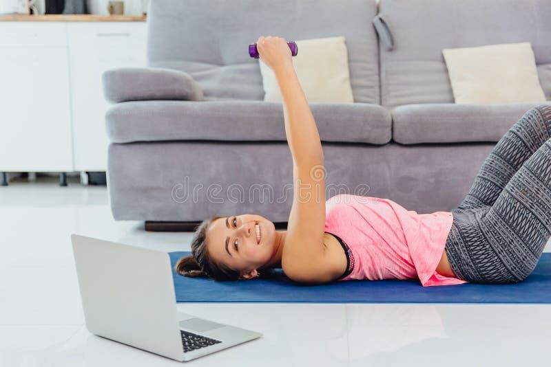 Junges Mädchen, das Laptop betrachtet und zu Hause Übungen tut stockfoto