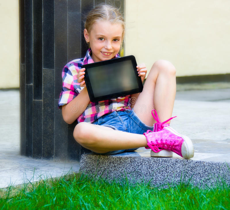 Junges Mädchen, das mit einer Tablette sitzt lizenzfreie stockfotografie