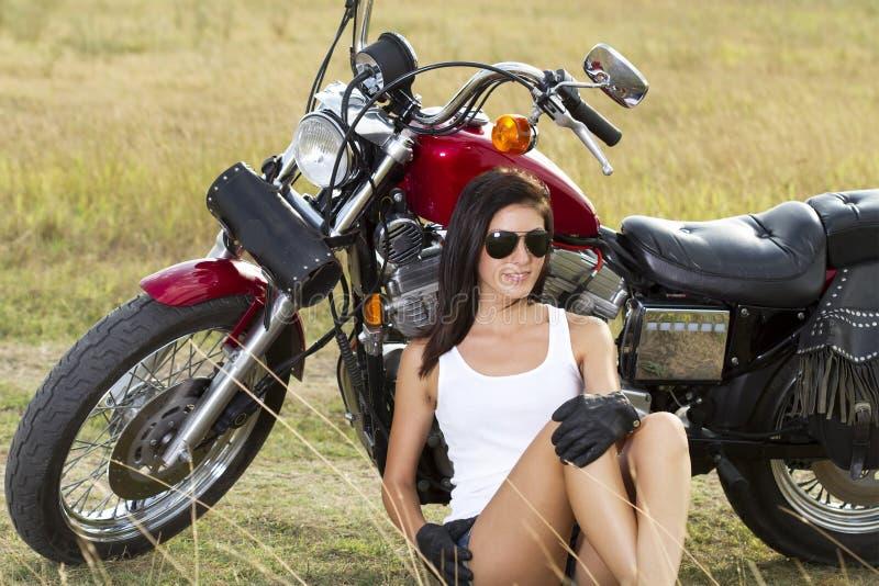 Junges Mädchen, das nahe einem Motorrad steht lizenzfreies stockbild