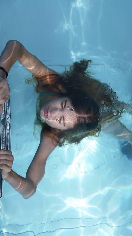 Junges Mädchen, das oben auf Poolleiter klettert lizenzfreie stockfotografie