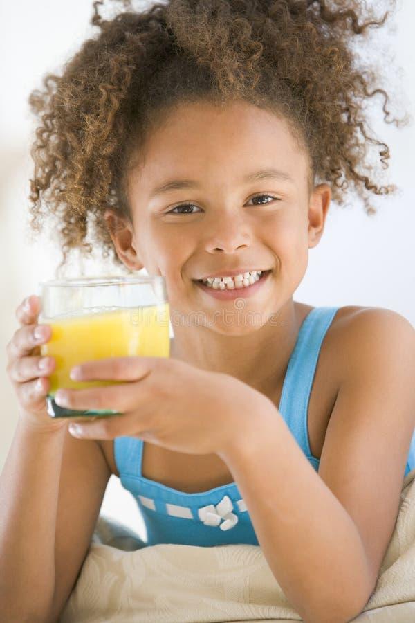 Junges Mädchen, das Orangensaft im Wohnzimmer trinkt lizenzfreies stockfoto