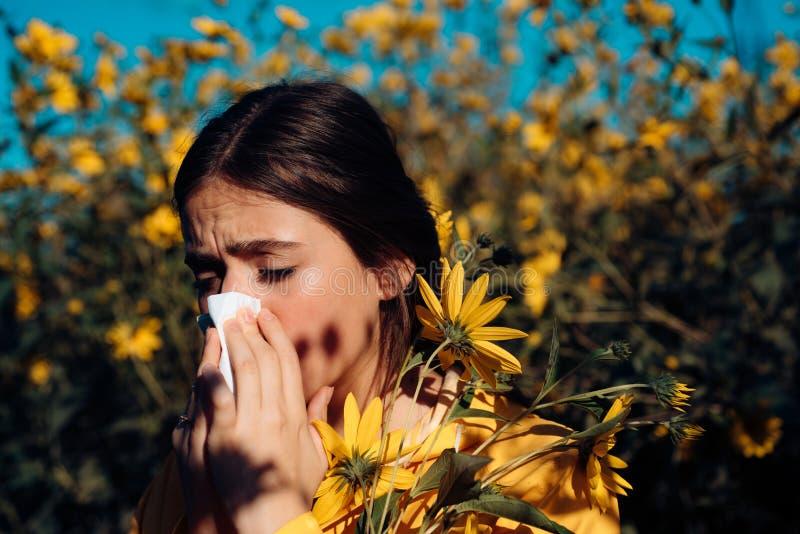 Junges Mädchen, das Papiergewebe in einem Hand- und Blumenblumenstrauß in anderem niest und hält Niesendes junges Mädchen mit Nas stockbild