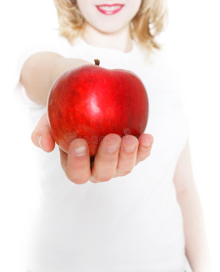 Junges Mädchen, das roten Apfel gibt stockfotografie