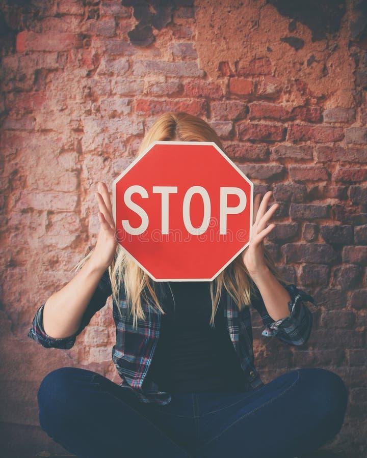 Junges Mädchen, das rotes Stoppschild hält gegenüberzustellen stockfotografie