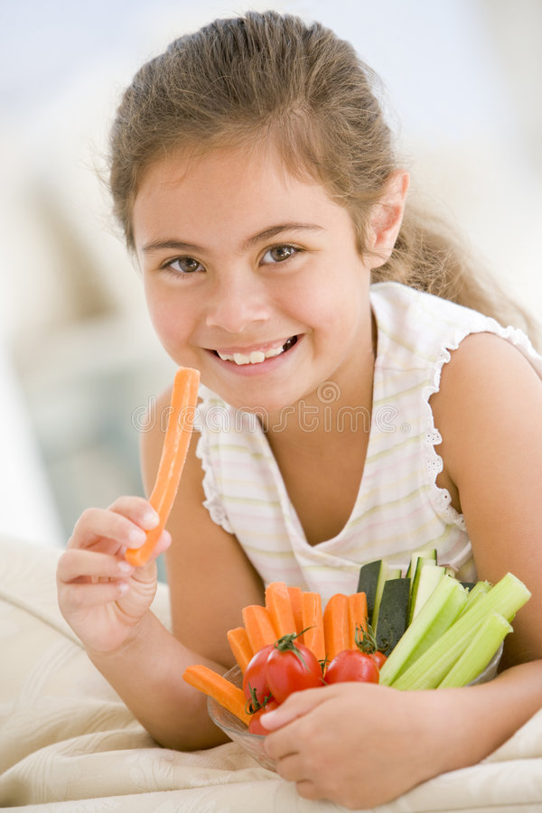 Junges Mädchen, das Schüssel Gemüse isst stockfotografie