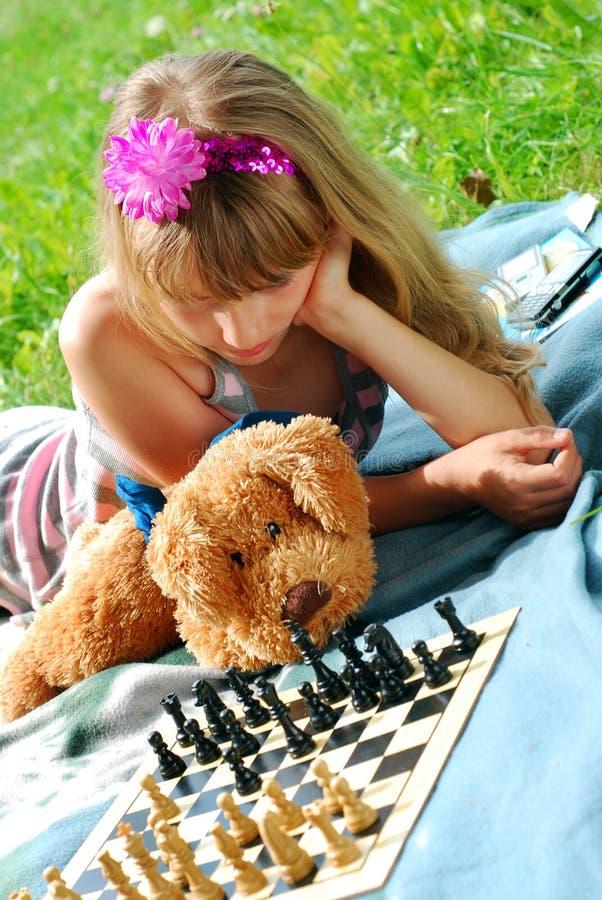 Junges Mädchen, das Schach spielt lizenzfreie stockfotografie